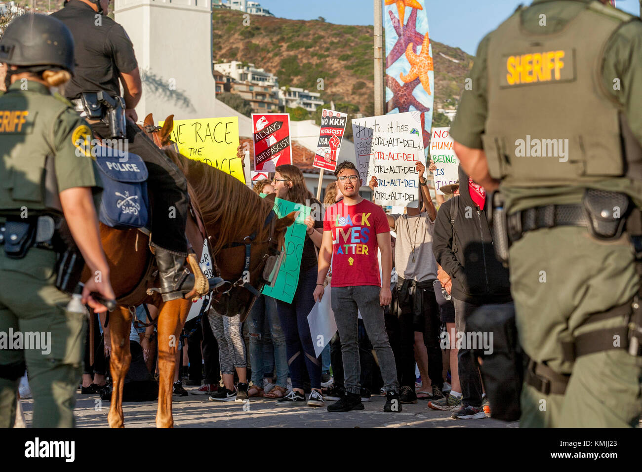 Multiracial counter demonstrators display their signs in Laguna Beach, CA, in opposition to an adjacent anti-immigrant - Stock Image