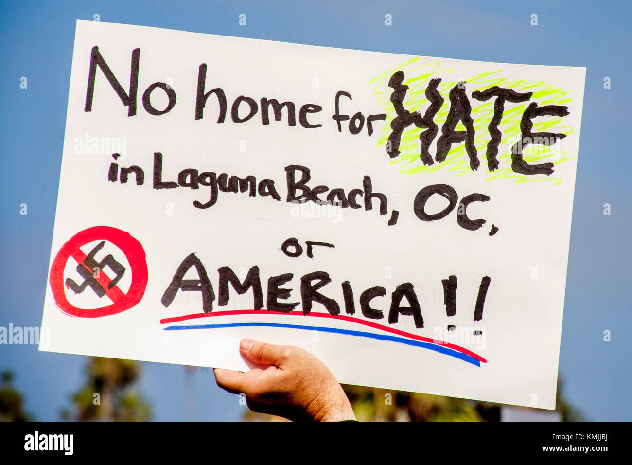 A counter demonstrator's sign expresses toleration at an anti-immigration rally in Laguna Beach, CA. - Stock Image
