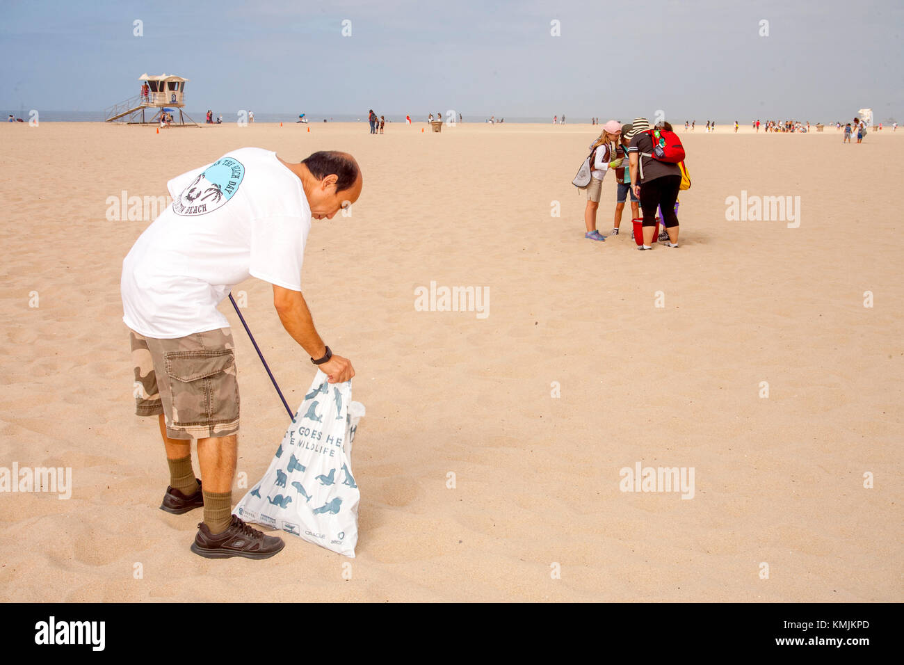 An Asian American volunteer bags trash at a weekend cleanup in Huntington Beach, CA. Note teen girls in background - Stock Image