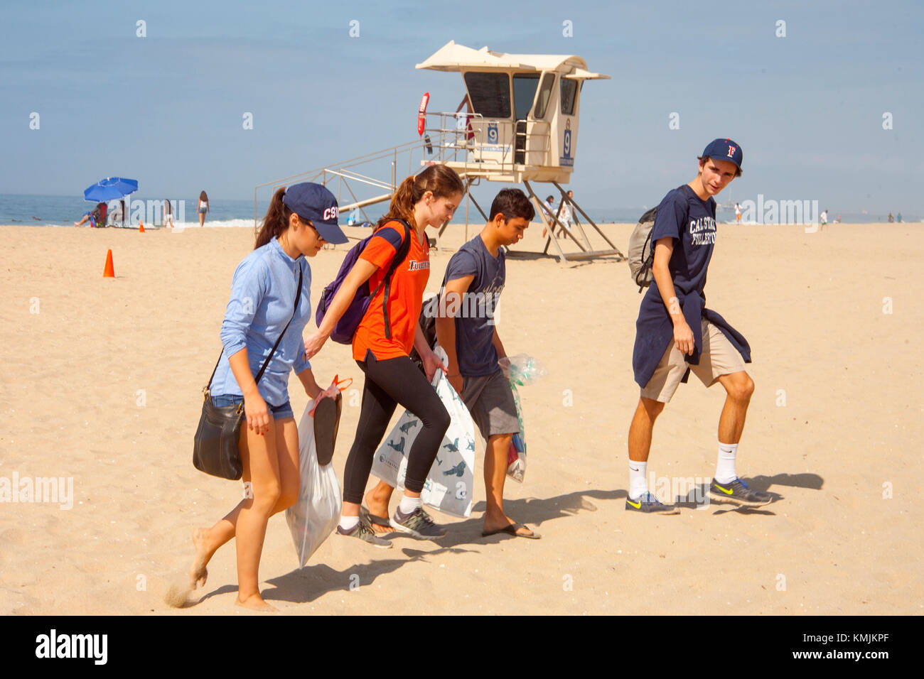 Teen volunteers carry trash at a weekend cleanup in Huntington Beach, CA. Note lifeguard station in background. - Stock Image