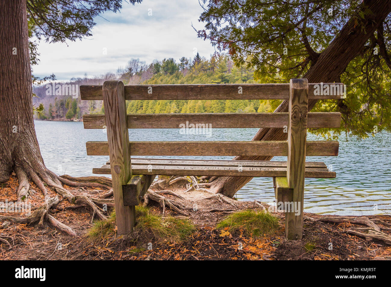 Serene setting, a park bench overlooking a calm lake. Green Lakes, Syracuse NY - Stock Image