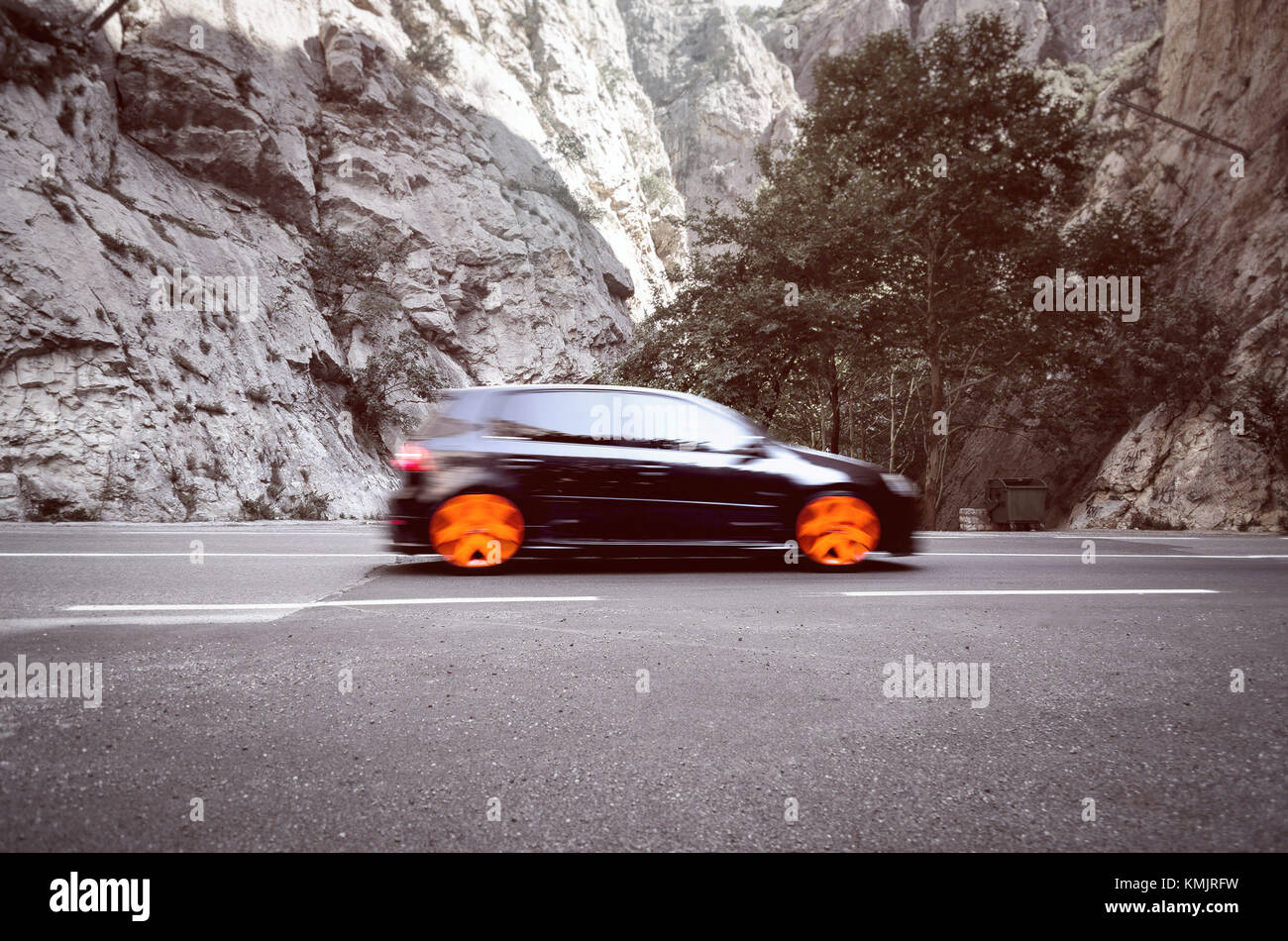 Fast sport hatchback car fasting through mountain pass - Stock Image