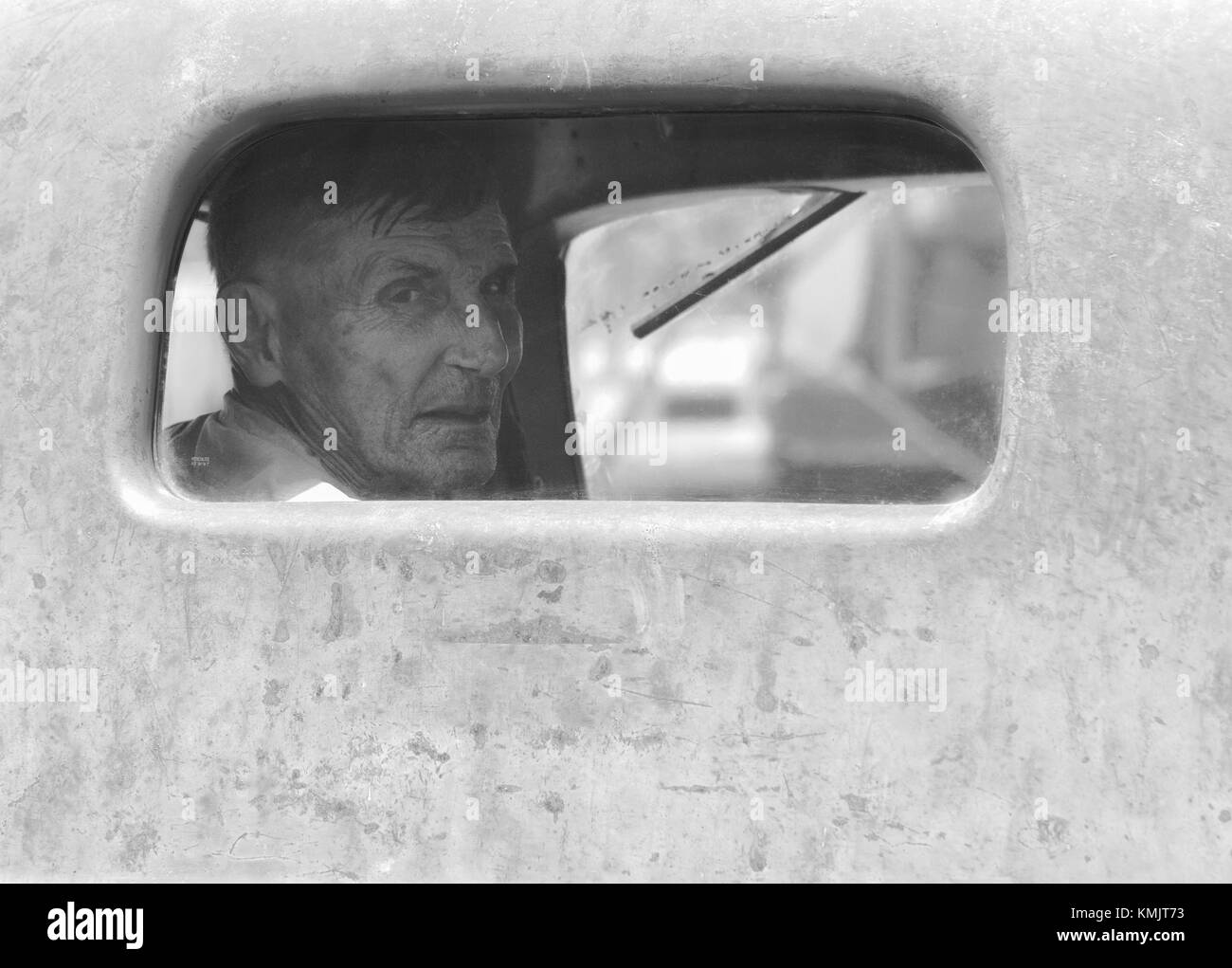 McMinnville, Oregon, USA - August 13, 2016:  An elderly man looks out the rear window of an old truck at Yamhill - Stock Image