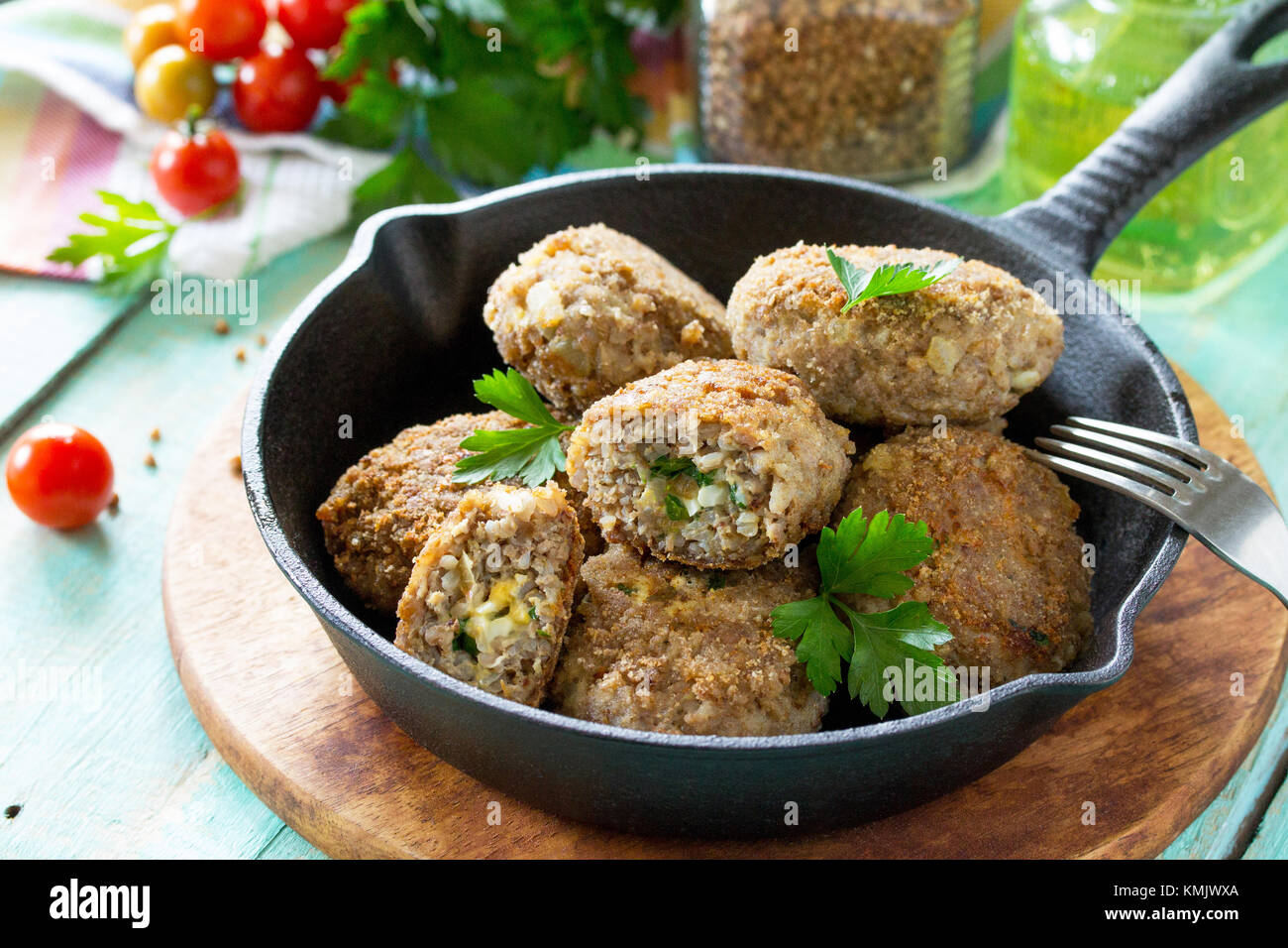 Homemade meatballs with buckwheat and egg stuffing. Cast-iron frying pan with delicious fried cutlets, fresh herbs - Stock Image