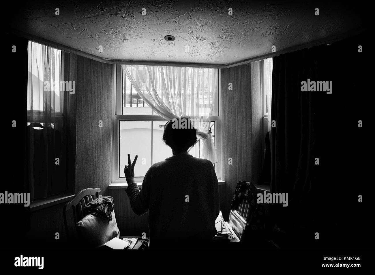 Rear view of woman showing victory sign inside a room, looking through window. London, England - Stock Image