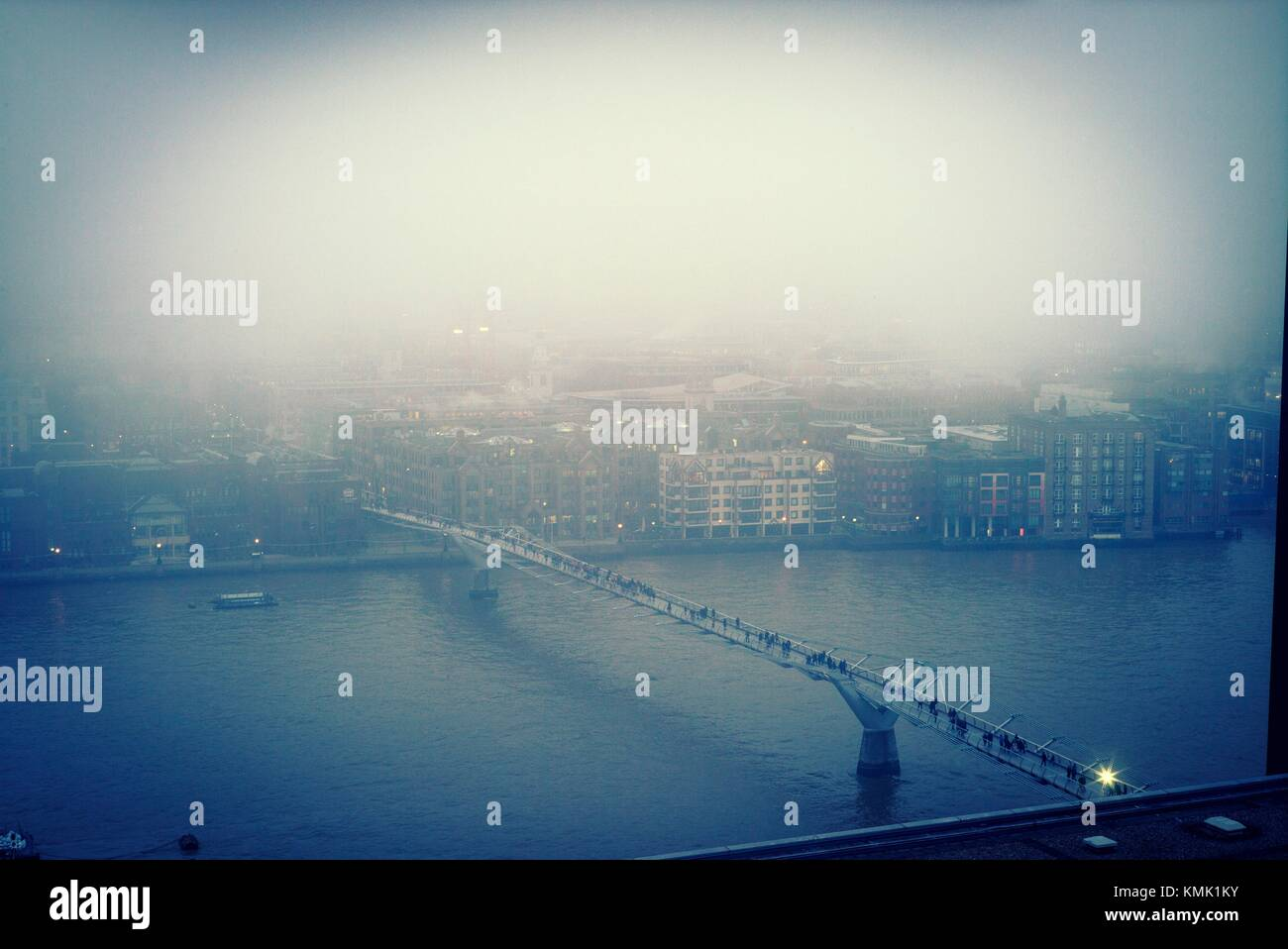 Evening View of the City with River Thames and Millennium Bridge amidst the fog. City of London, Square Mile, West - Stock Image