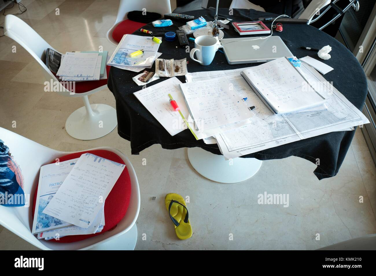 Messy working desk with many objects: paper, laptop computer, cup, etc. Barcelona, Catalonia, Spain - Stock Image