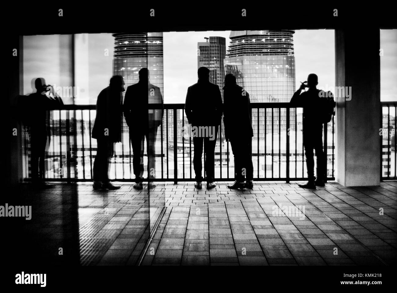 Silhouette of unrecognizable three man and reflected on a glass looking at the City from a balcony. Tate Modern, The City, Bankside, London, UK Stock Photo