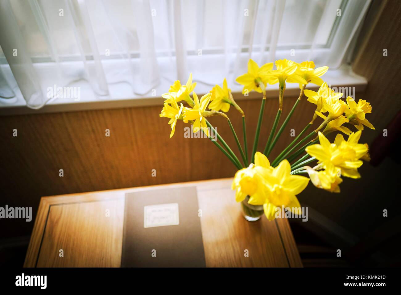 Table beside window with book and vase with yellow flowers inside house. London England & Table beside window with book and vase with yellow flowers inside ...