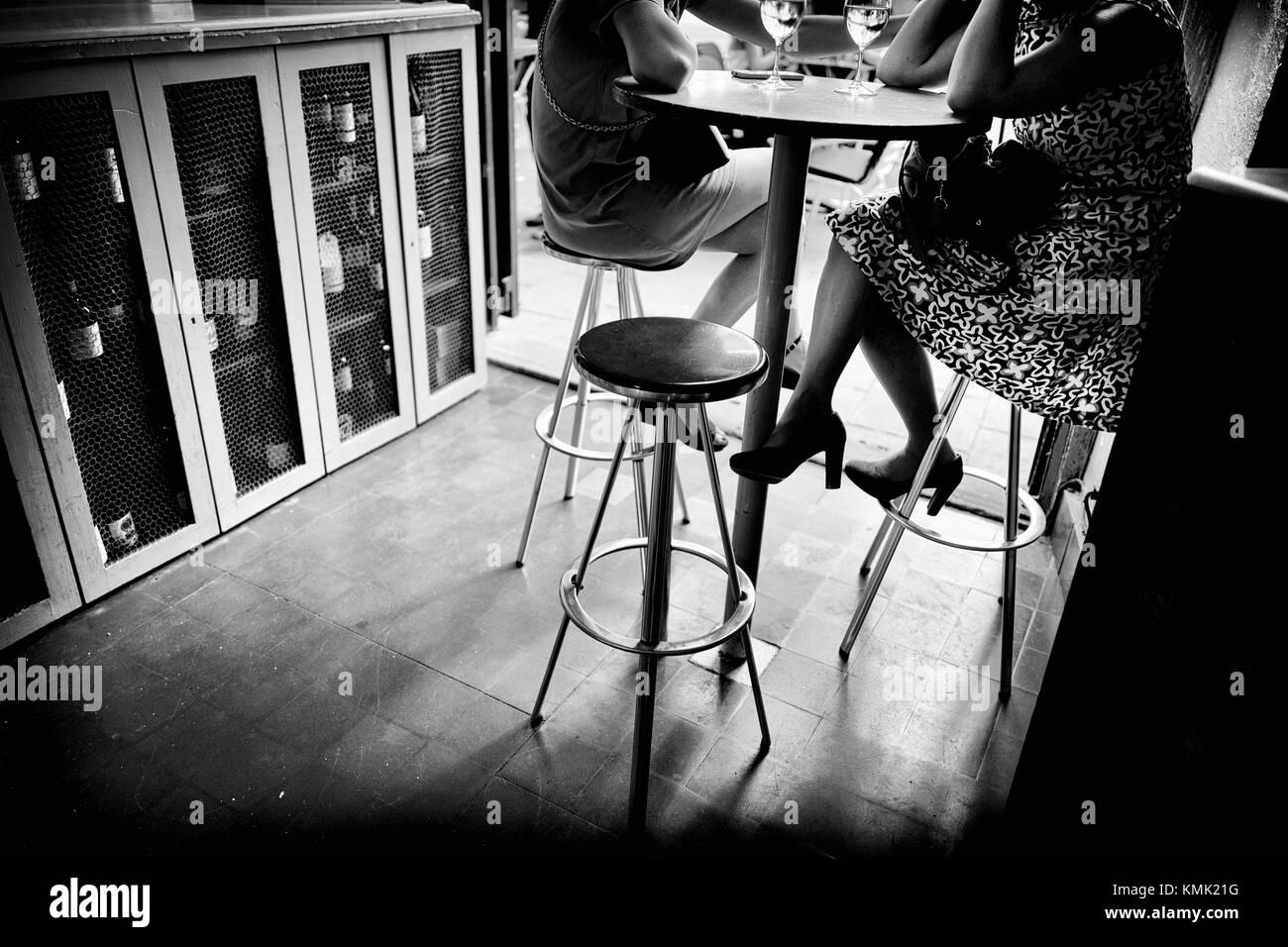 Dos mujeres jovenes irreconocibles tomando una copa de vino en un bar sentadas en un taburete. Barcelona, Catalonia, Stock Photo