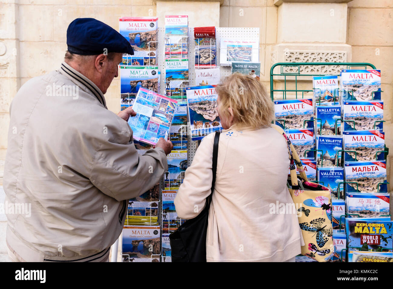 British English tourists look at guide books for sale outside a shop in Valletta, Malta - Stock Image