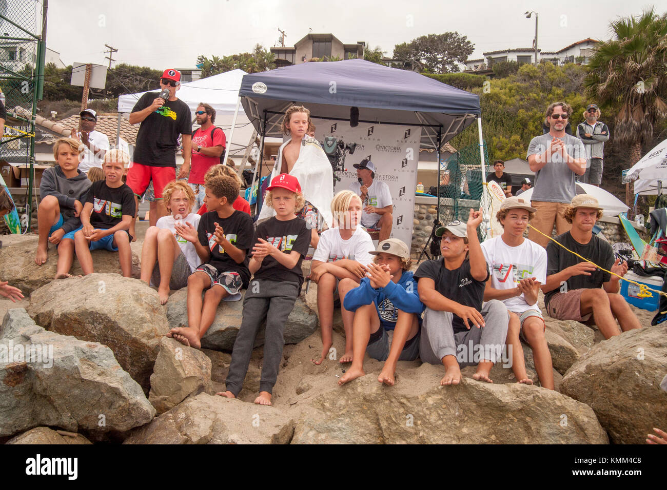 A frieze of boys watches a surfing competition in Laguna Beach, CA. - Stock Image