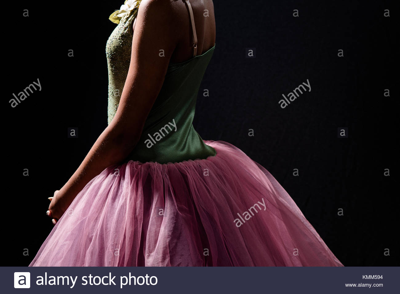 torso of a teen girl in a ballet tutu on a black background - Stock Image