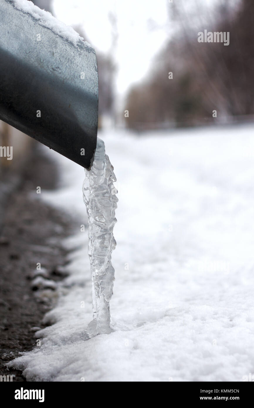 Winter city fragment. Icicles and frost on drainpipe . - Stock Image