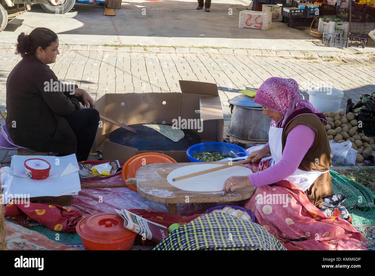 Turkish woman cooking Pide (flat bread) at the market of Ocurcalar, turkish riviera, Turkey - Stock Image