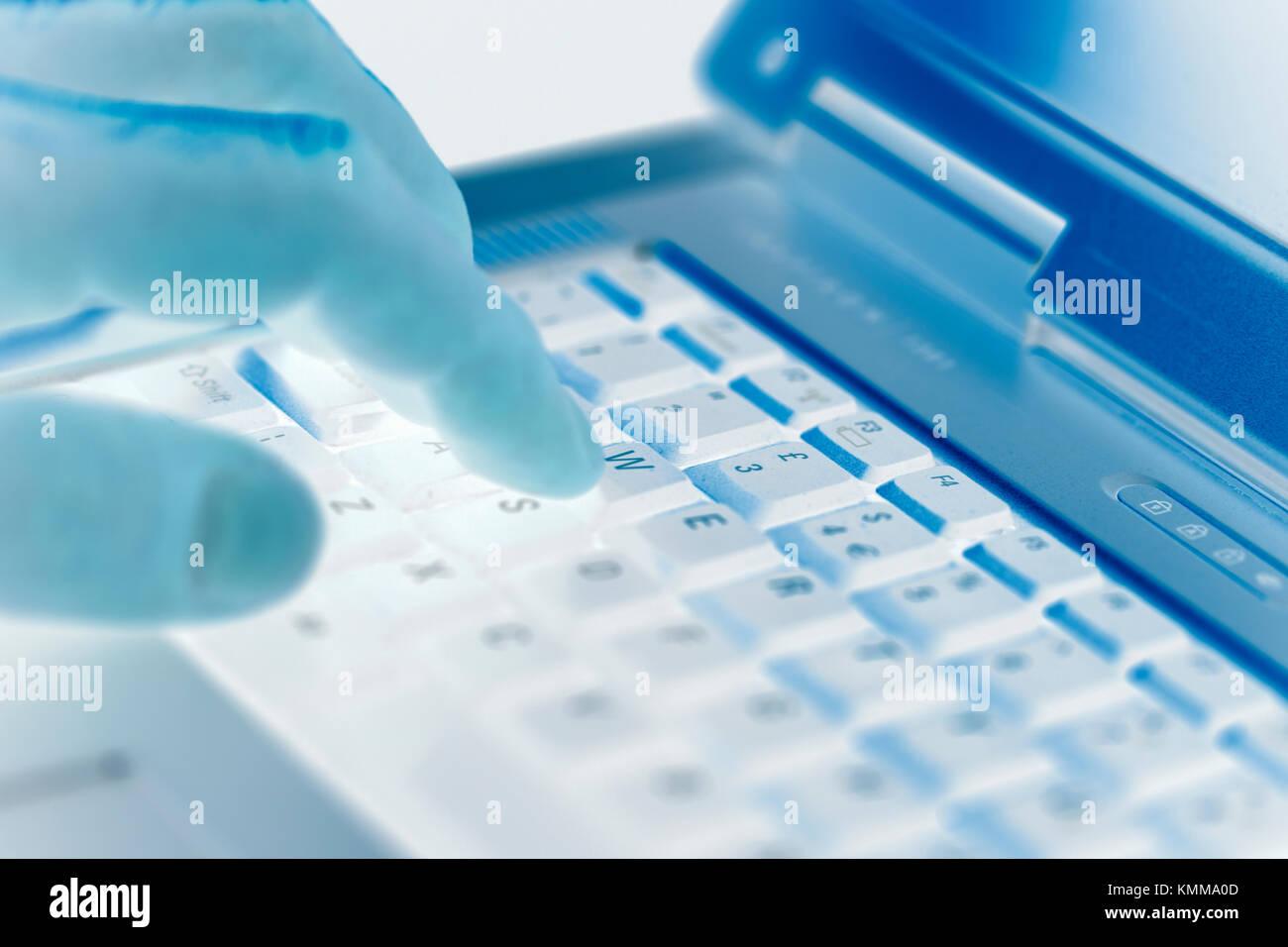 Man pressing a key on a laptop keyboard - Stock Image