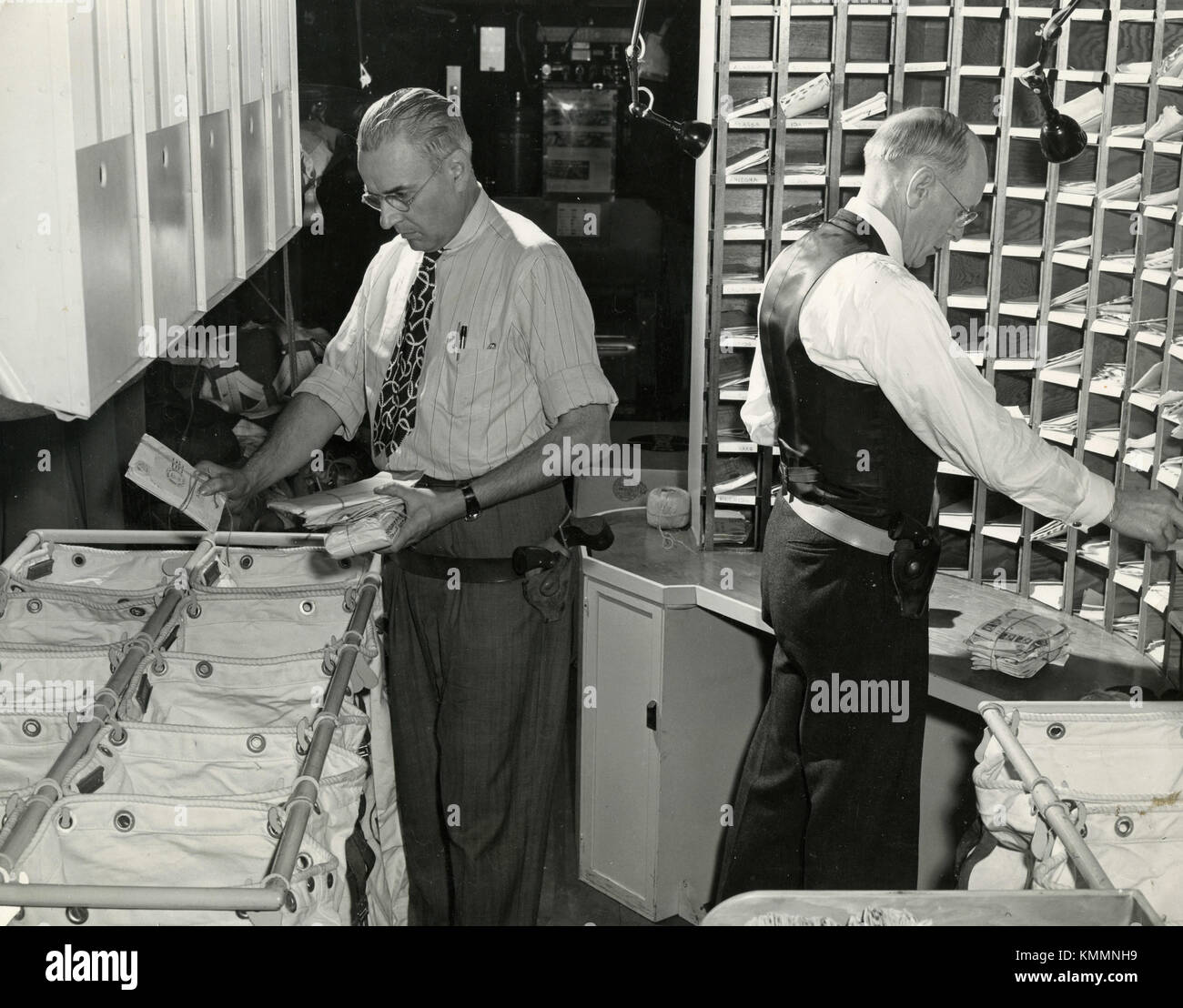 Inside the aircraft Fairchild C-82 Packet two postal service clerks sort the mails, USA 1940s - Stock Image