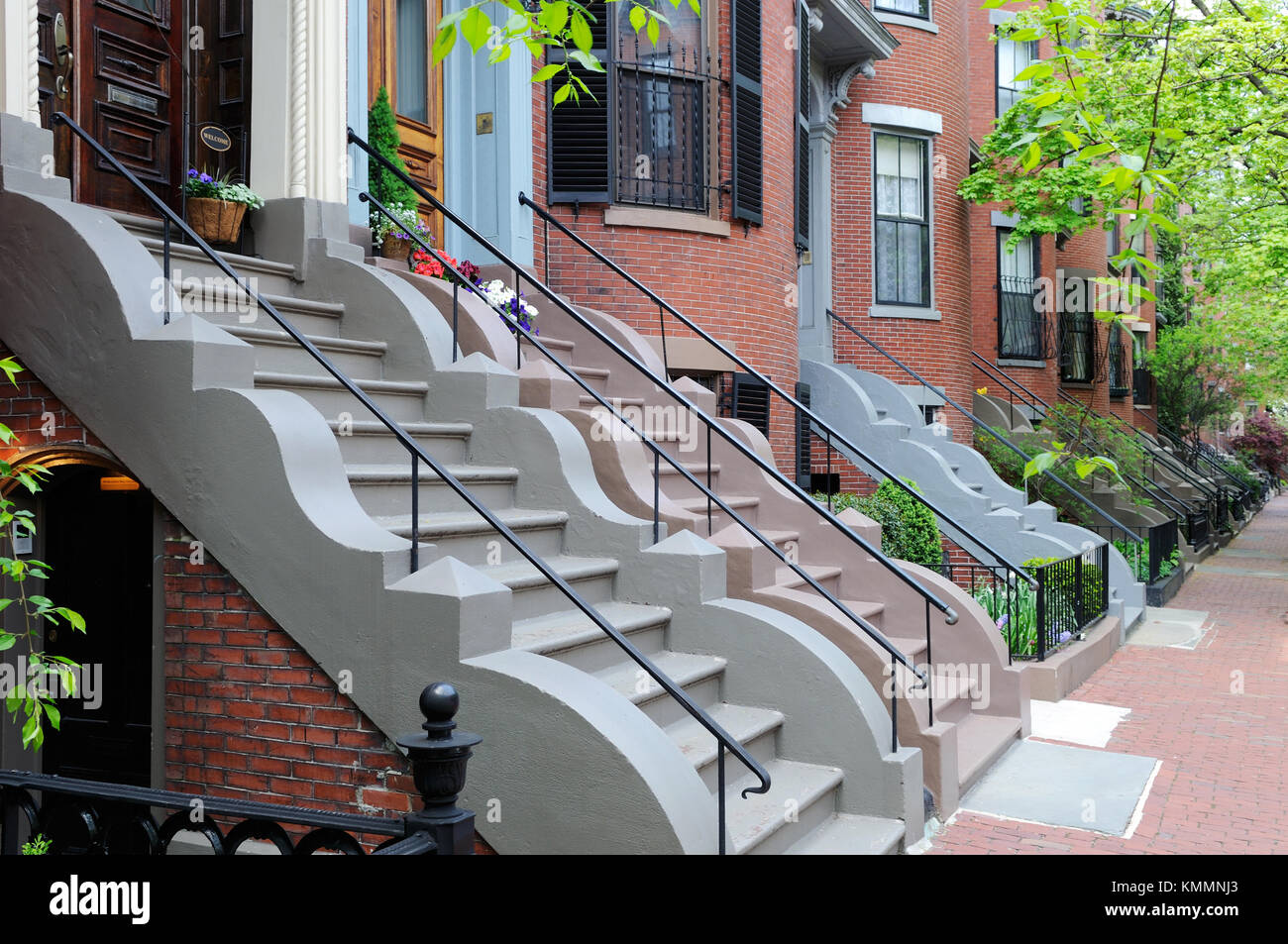 South End, Boston Victorian row houses. Brick aparment buildings and sidewalks, colorful steps with wavy stone trim, Stock Photo