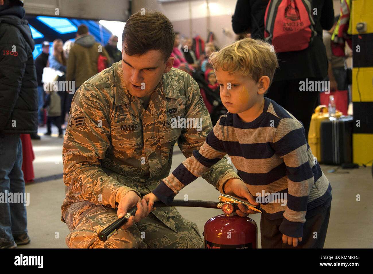 U.S. Air Force Senior Airman Seth Warner, 86th Civil Engineer Squadron driver operator, helps a child from the Kaiserslautern - Stock Image