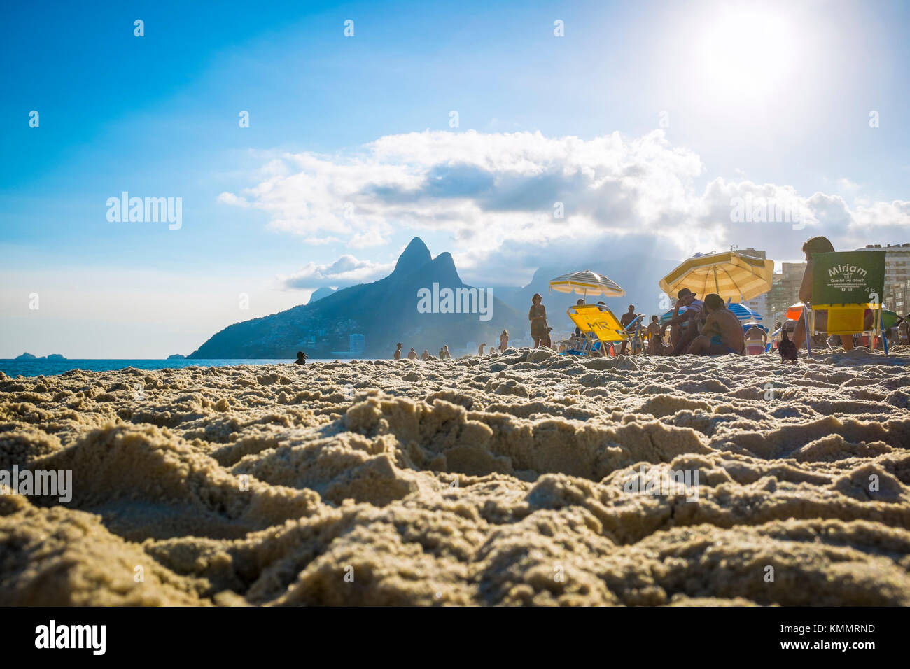 RIO DE JANEIRO - MARCH 06, 2016: People relax on Ipanema Beach against the iconic silhouette of Two Brothers Mountain - Stock Image