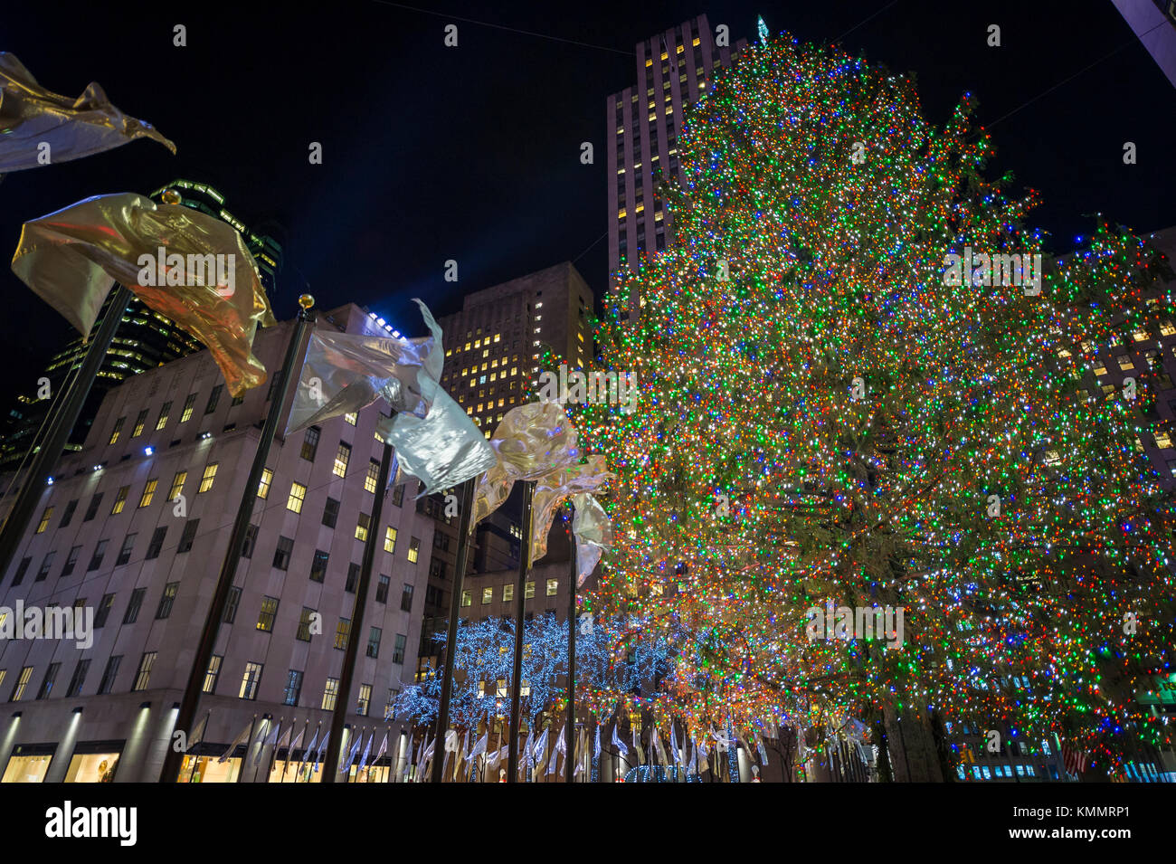 Holiday flags fly around the central plaza in front of the Rockefeller Center Christmas Tree, one of New York City's - Stock Image