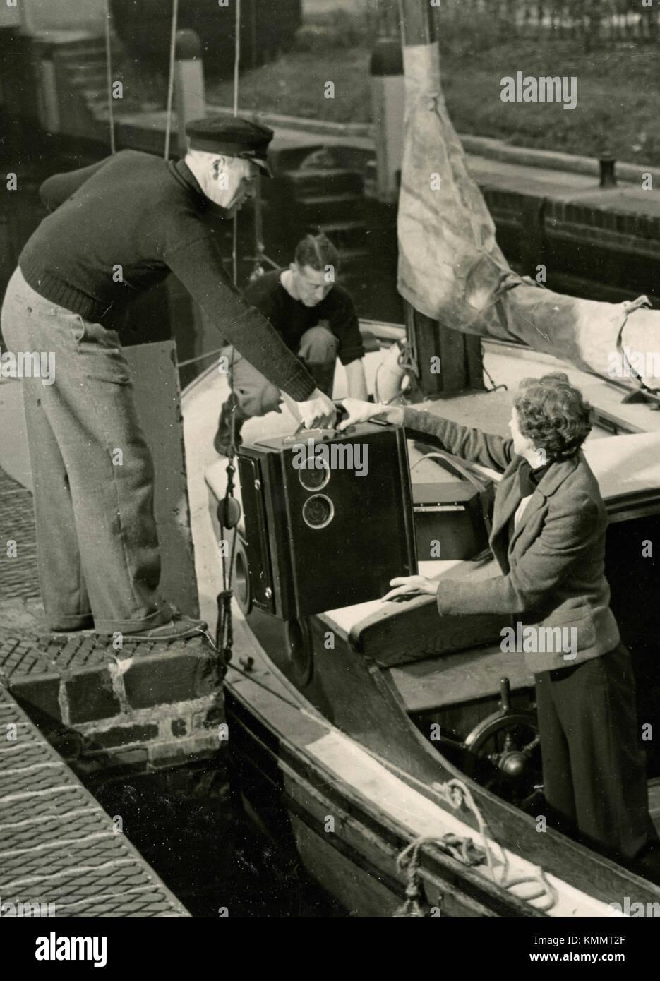 Amateur yachtsman embarking battery driven portable navigator, UK 1950s - Stock Image