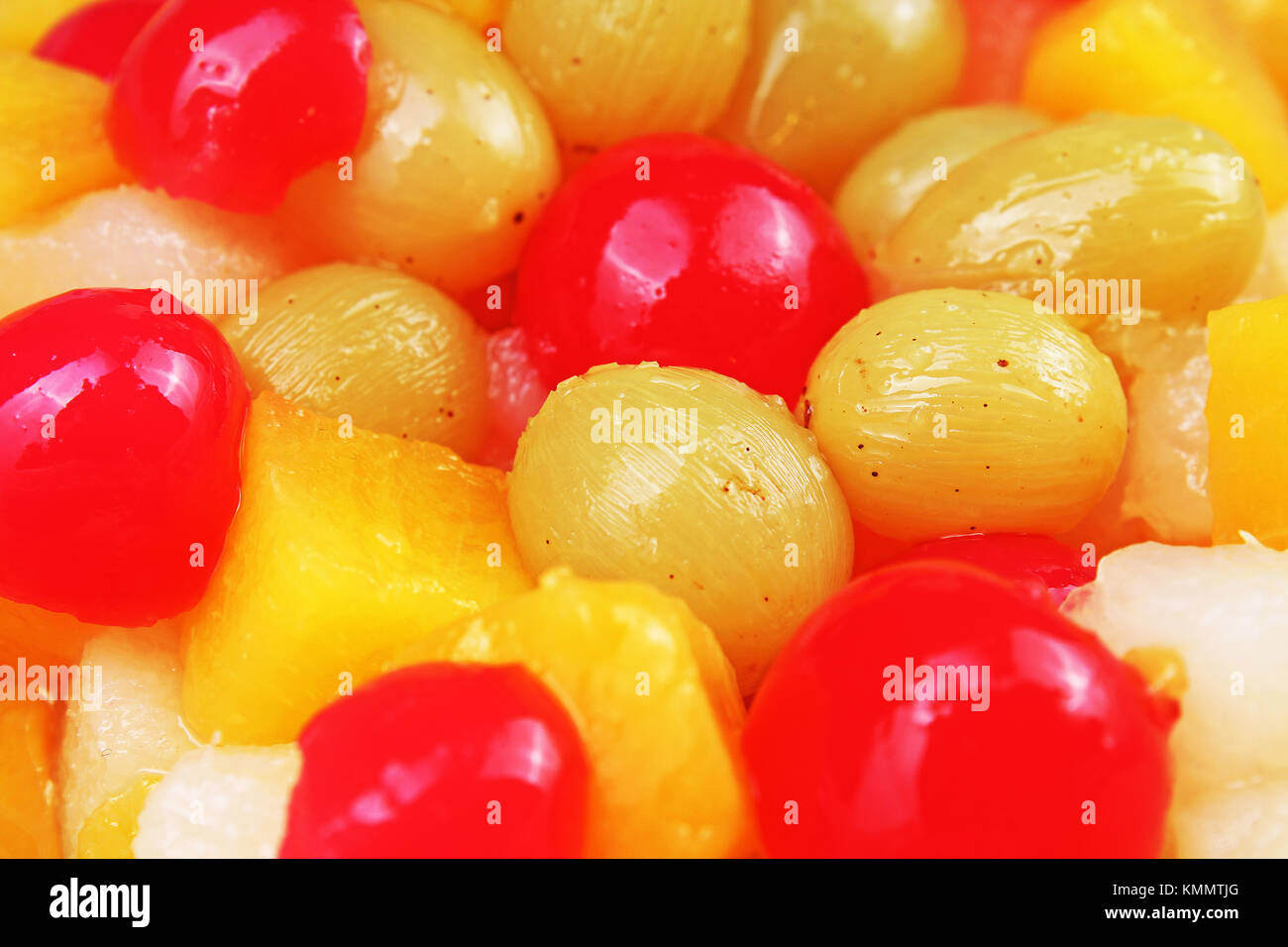 Fruit salad texture. Fruits as background pattern. Exotic Fruits Fruit salad with cocktail cherry sour cherry mango - Stock Image