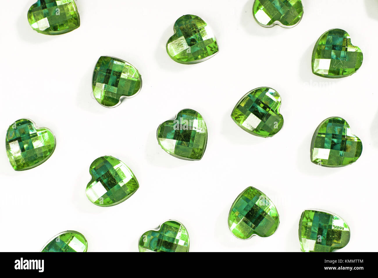 Green Rhinestone background. Heart shape texture as backdrop isolated white studio photo. Bling rhinestone crystal - Stock Image