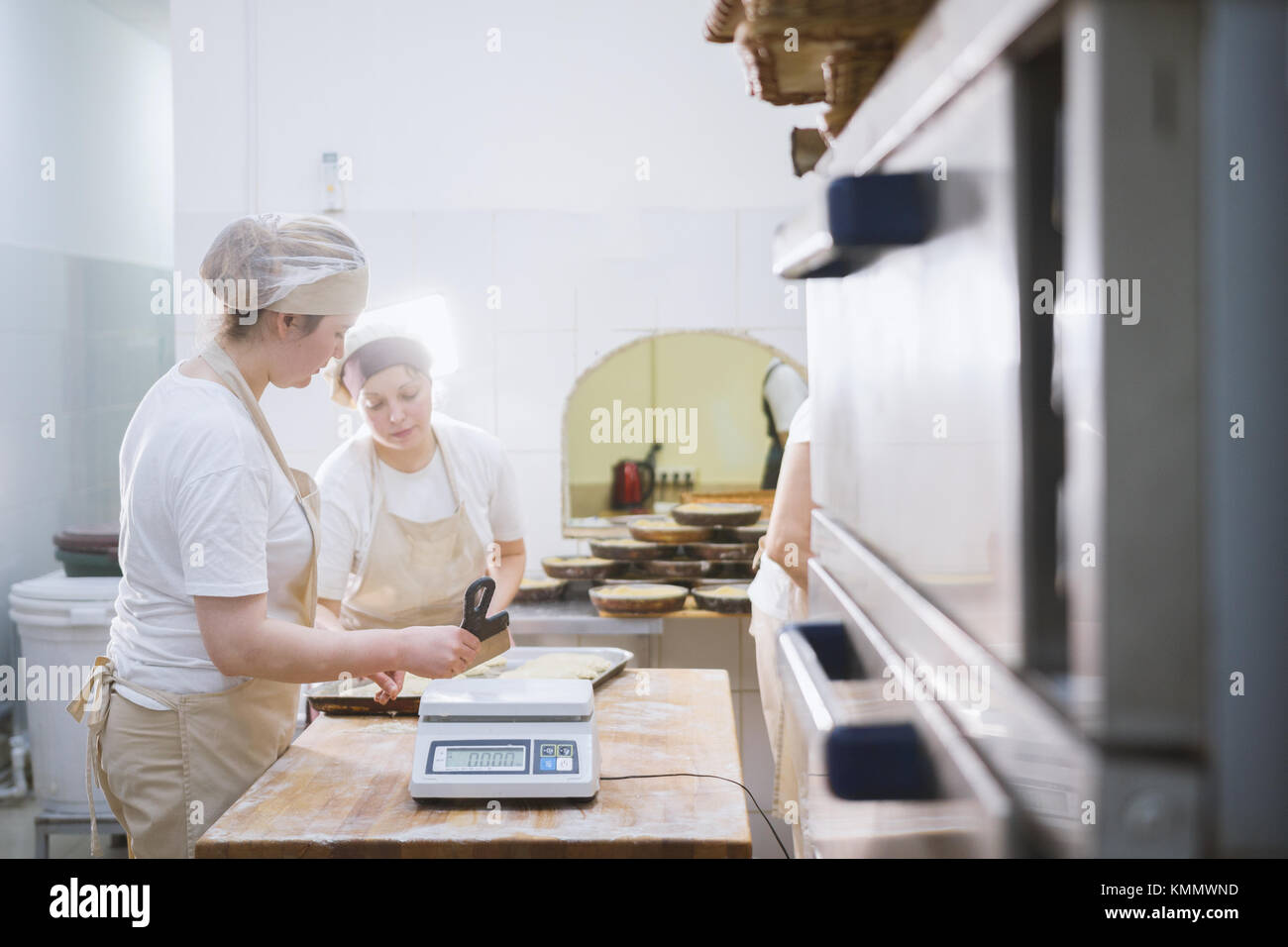 Smiling cooks work in the bakery - Stock Image