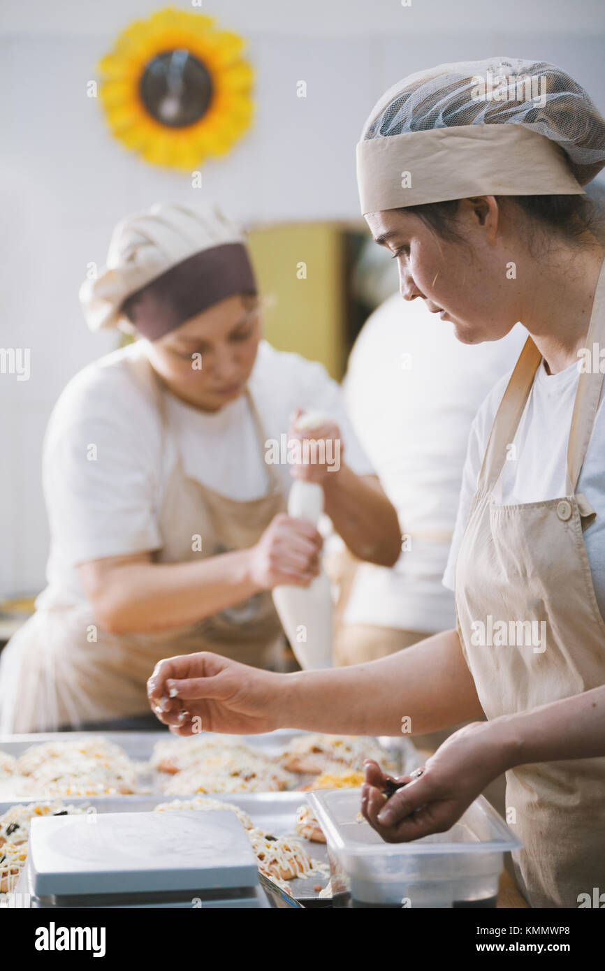 Cooks cook pizza in the bakery - Stock Image