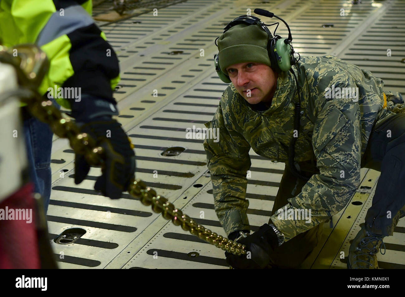 Master Sgt. Jeff Gilbert, 337th Airlift Squadron loadmaster, tightens down a chain connecting the Geostationary - Stock Image