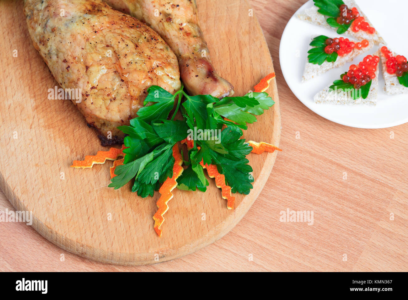 Fried chicken legs with parsley and red caviar - Stock Image