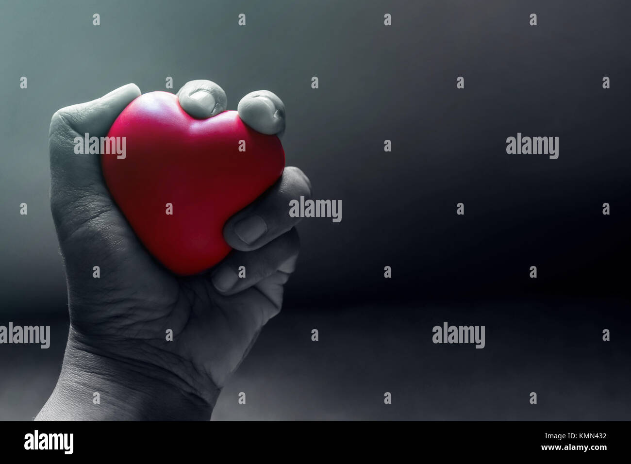 Love and Pain Concept, Hand Squeezing a Red Heart with Anger and Suffering in the Dark Light Room - Stock Image