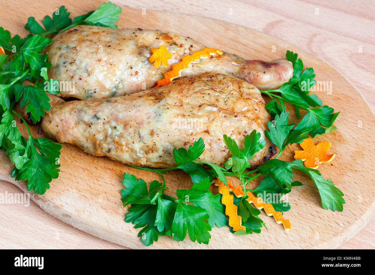 Fried chicken legs with parsley on the board - Stock Image
