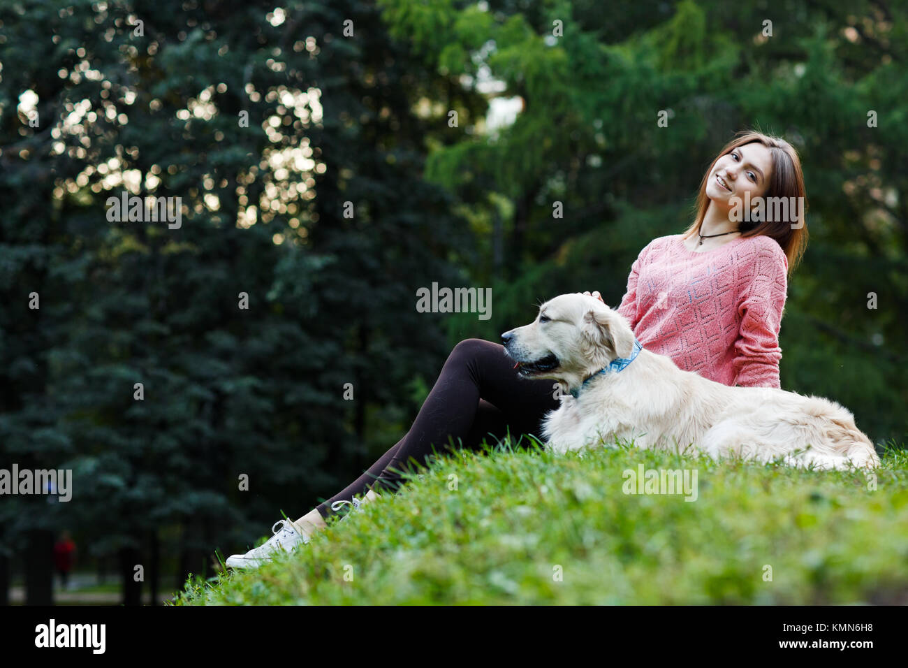 Photo from below of woman sitting with dog on green lawn - Stock Image