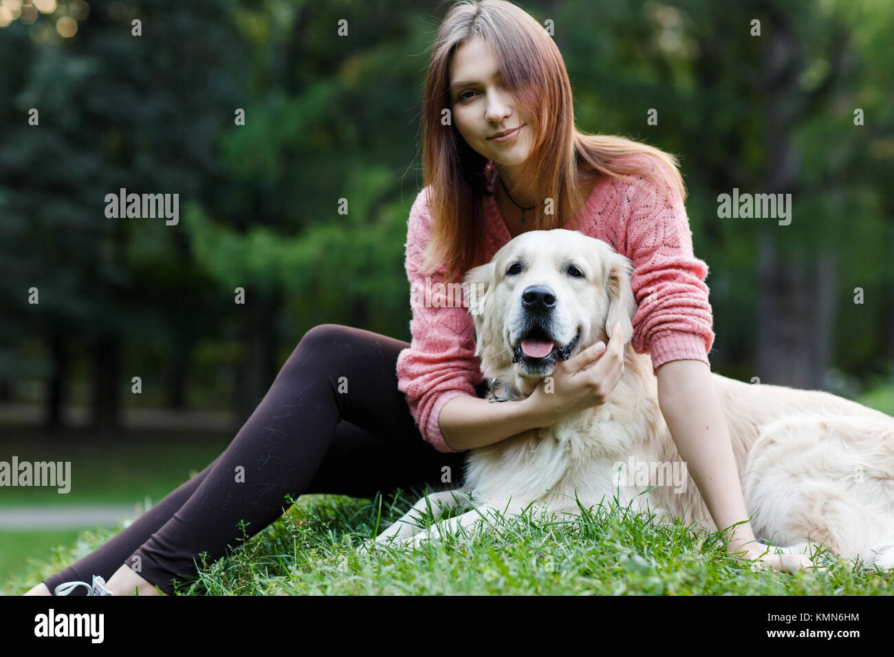 Image of woman and dog sitting on lawn - Stock Image
