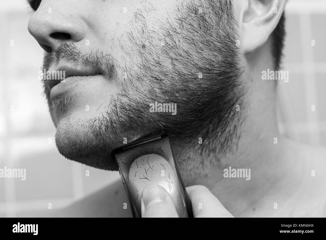 Portrait of young man shaving with trimmer Stock Photo