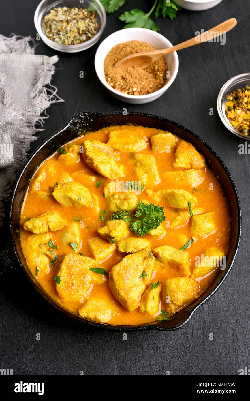 Delicious chicken curry in frying pan on dark stone table. - Stock Image