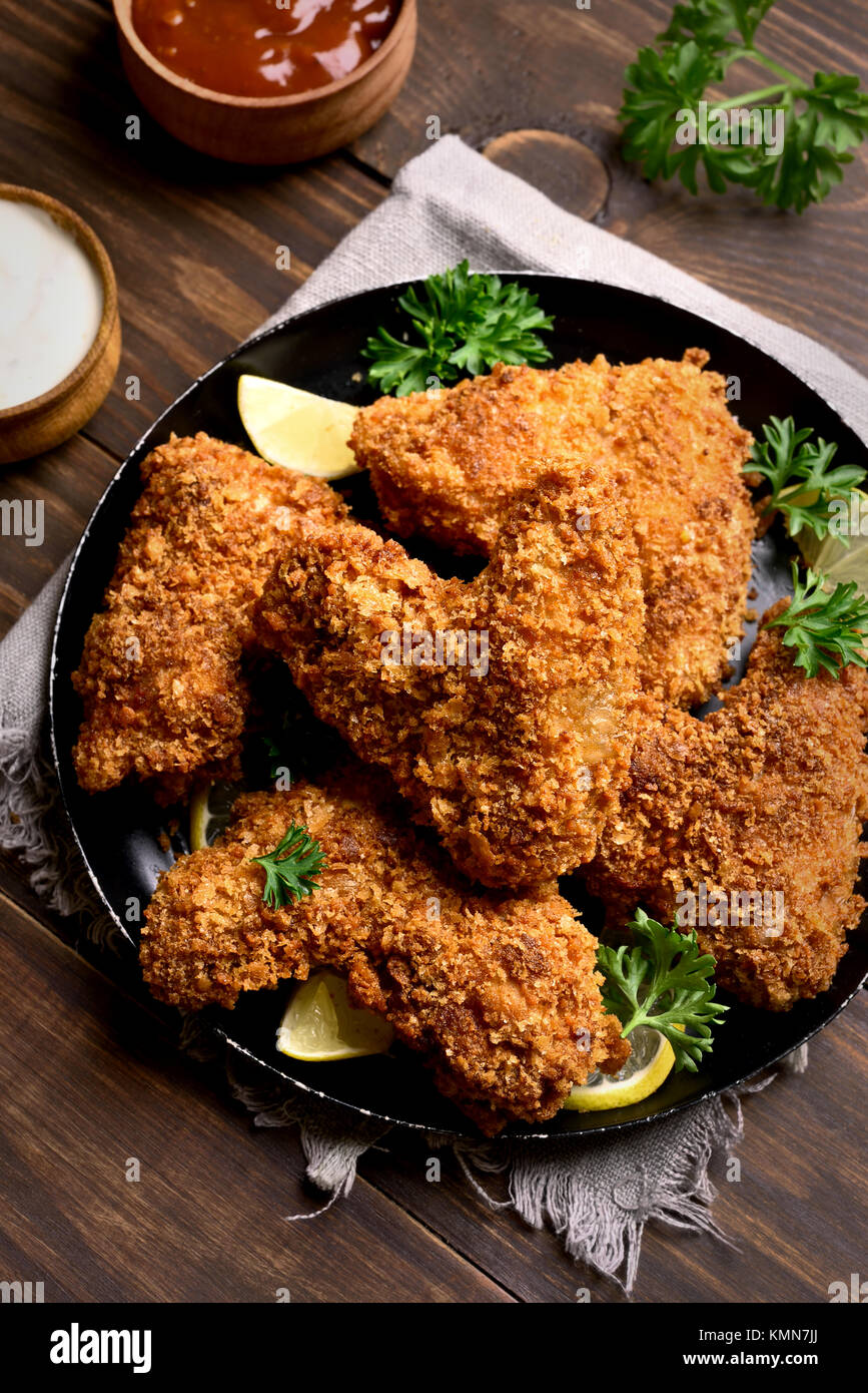 Crispy chicken wings. Dish for dinner on black plate - Stock Image