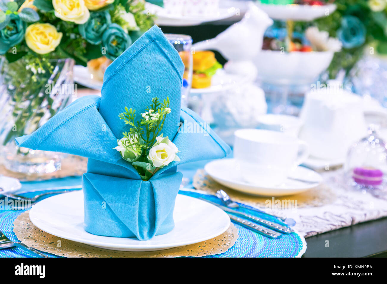 party table setting with a blue napkin flower white plate and white teacup in the celebration day. decoration dinner table served in blue tone color & party table setting with a blue napkin flower white plate and ...