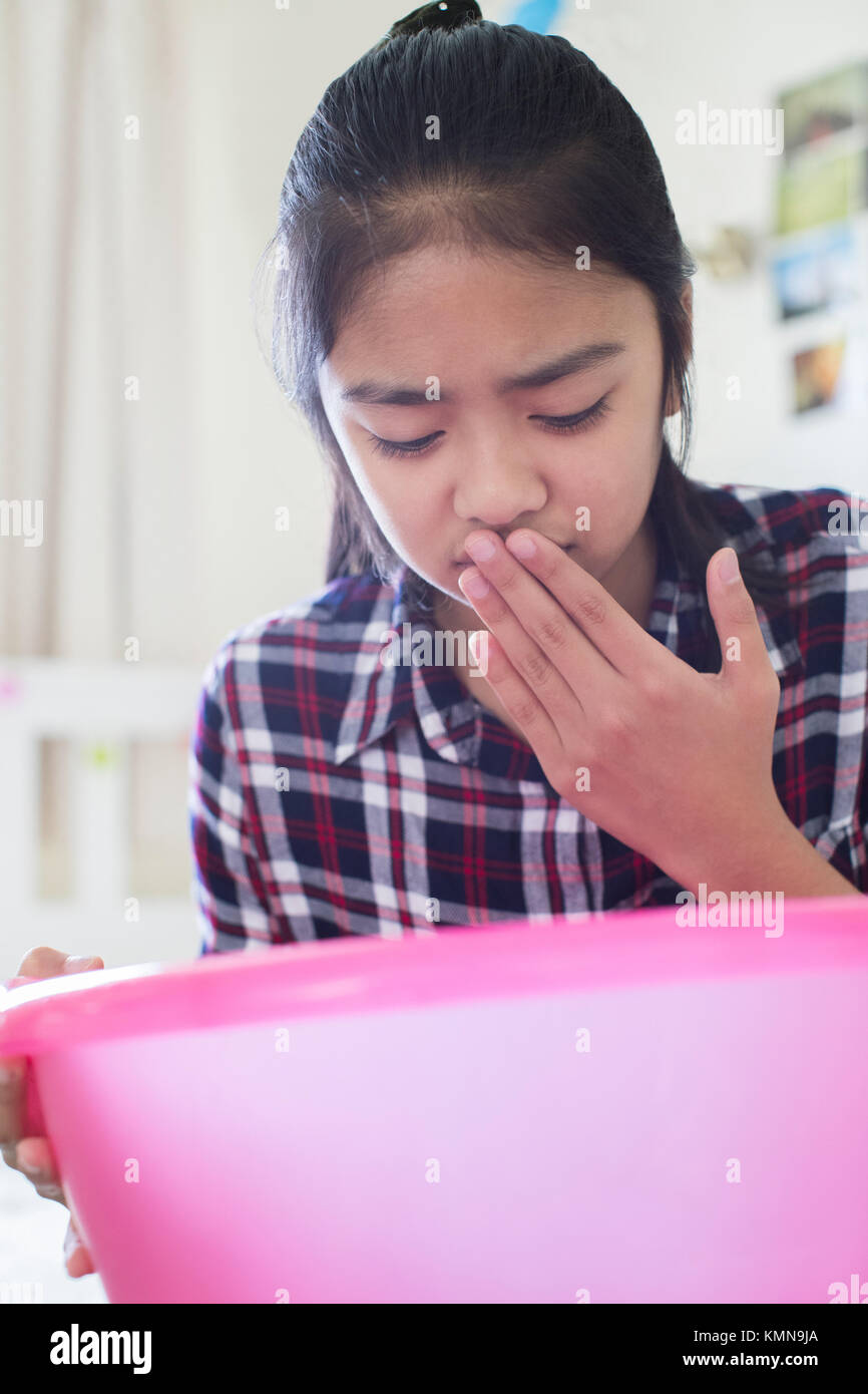 Young Girl Sitting On Bed At Home Feeling Nauseous - Stock Image