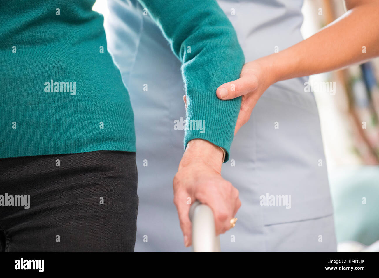 Senior Woman's Hands On Walking Frame With Care Worker In Background - Stock Image