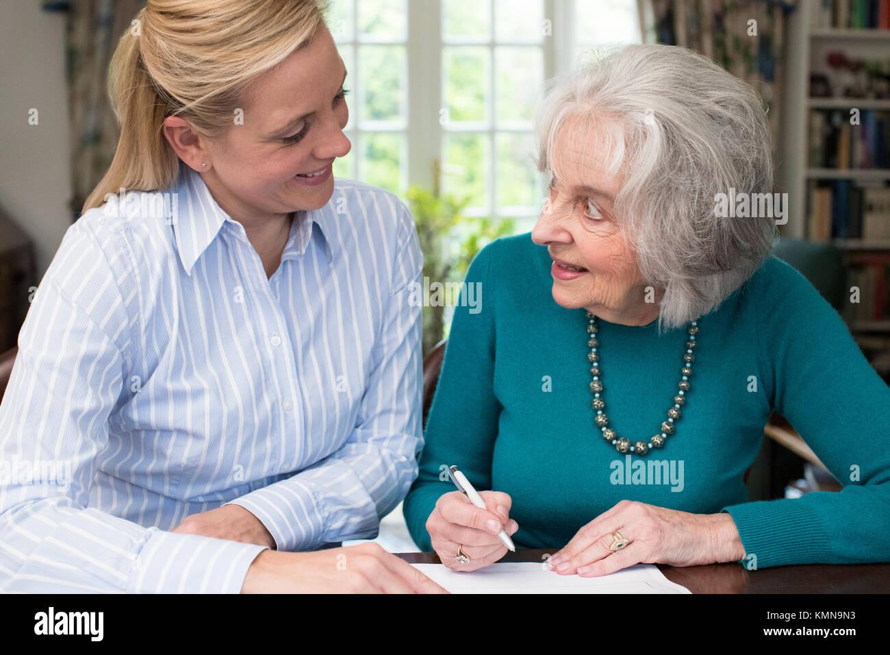 Woman Helping Senior Neighbour With Paperwork - Stock Image