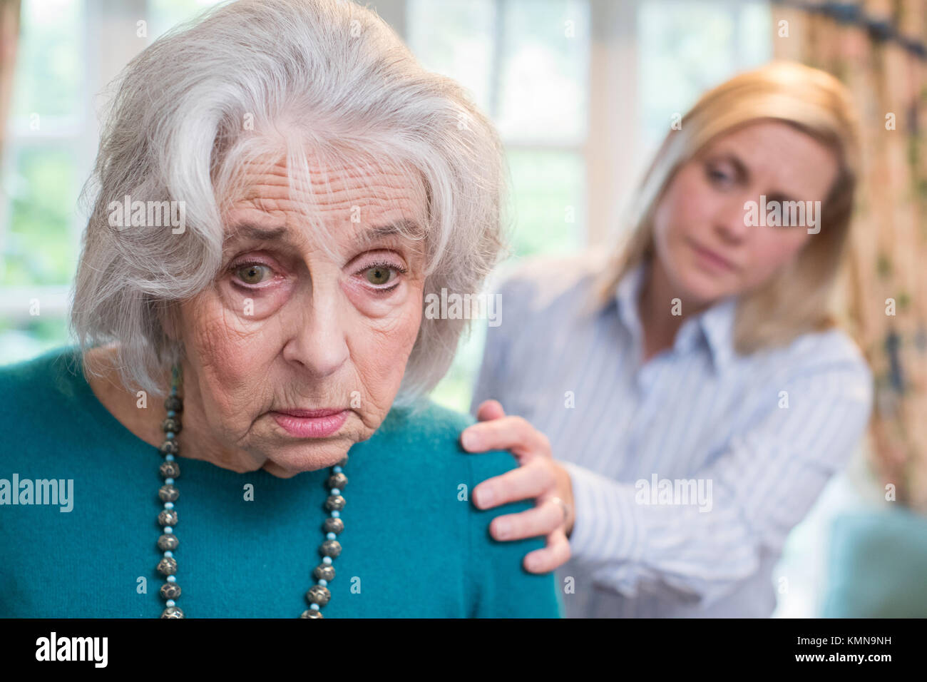 Confused Senior Woman With Adult Daughter At Home - Stock Image