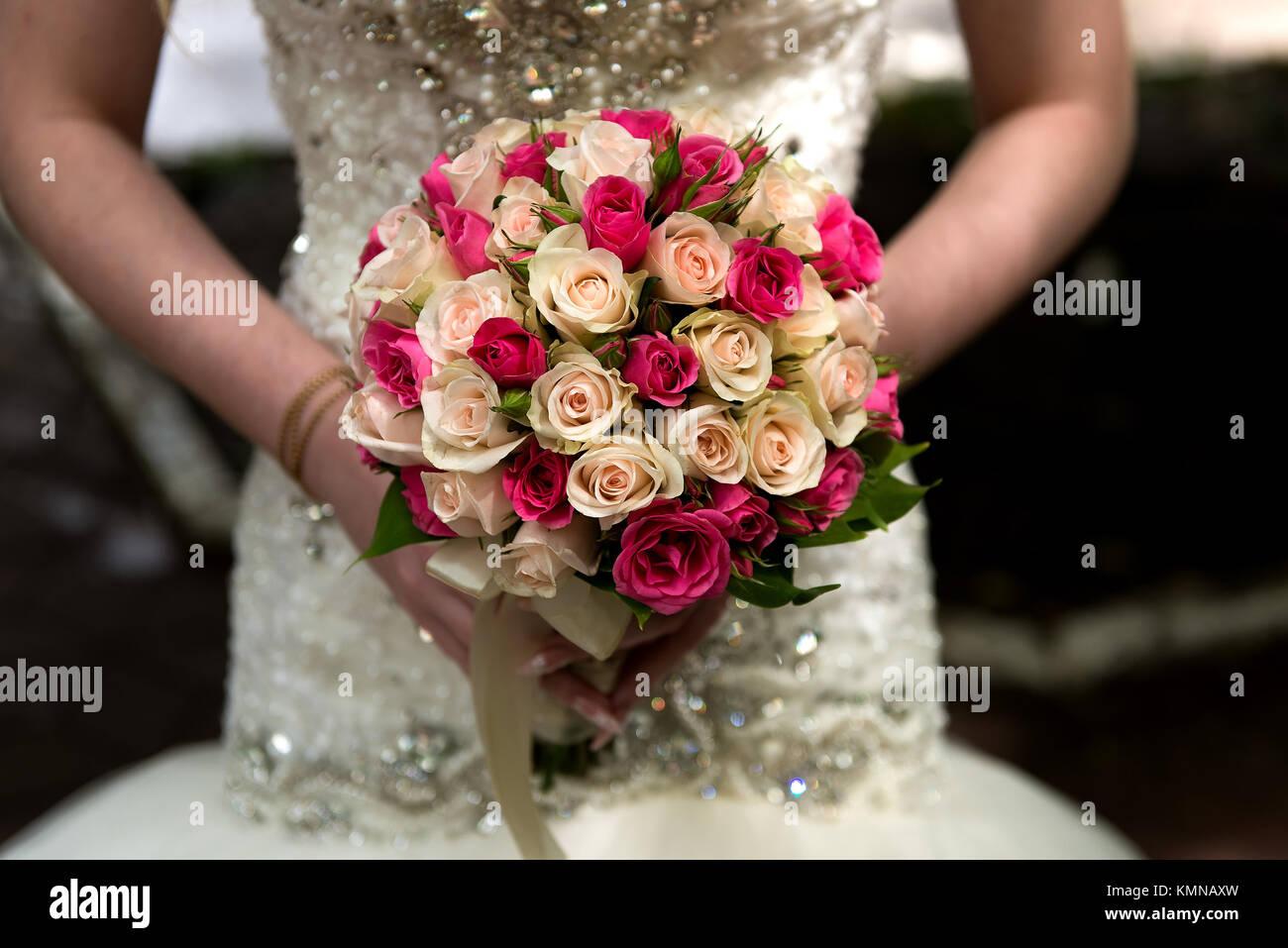 Beautiful bride holds wedding bouquet - Stock Image