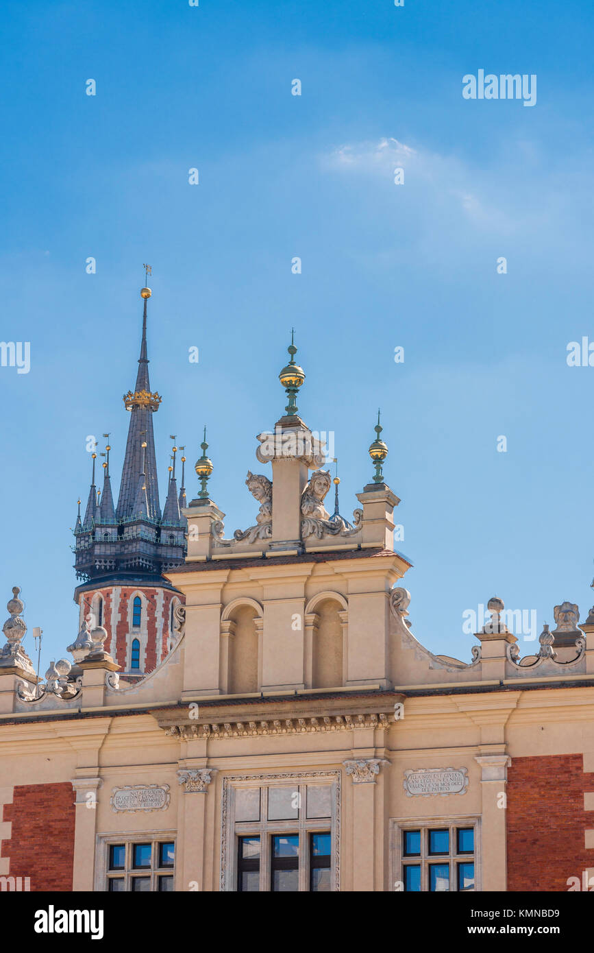 Krakow skyline, view of the gable above the grand portico of 16th Century Cloth Hall with St Mary's Church spire - Stock Image