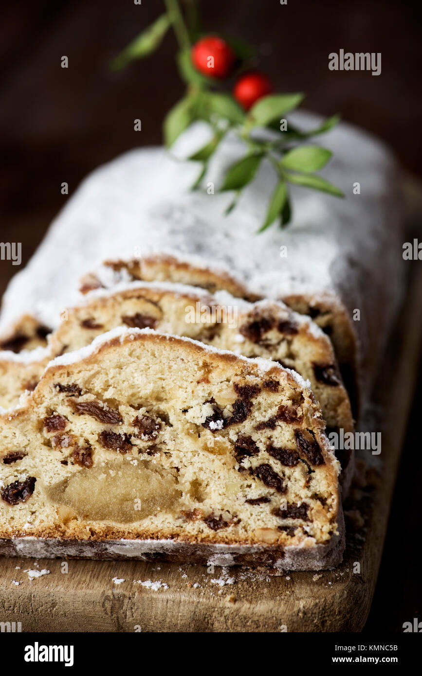 closeup of a stollen cake for christmas time sprinkled with icing sugar, placed on a wooden rustic table - Stock Image