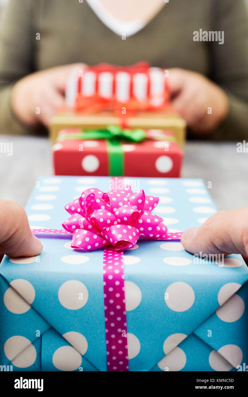 closeup of a young caucasian woman and a young caucasian man exchanging gifts on a gray rustic wooden table - Stock Image
