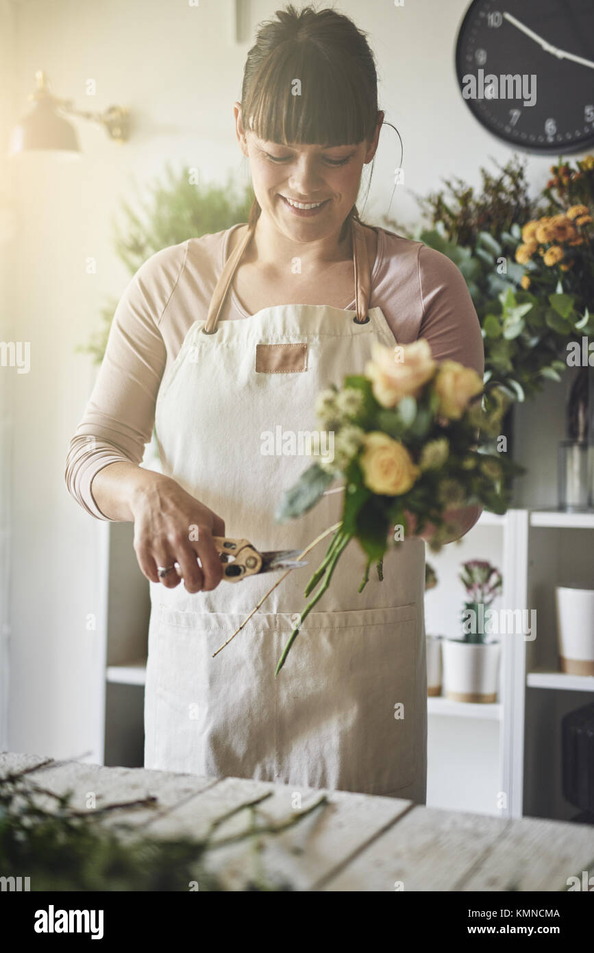 Smiling young female florist standing at a table in her flower shop trimming stems while making a bouquet of mixed Stock Photo
