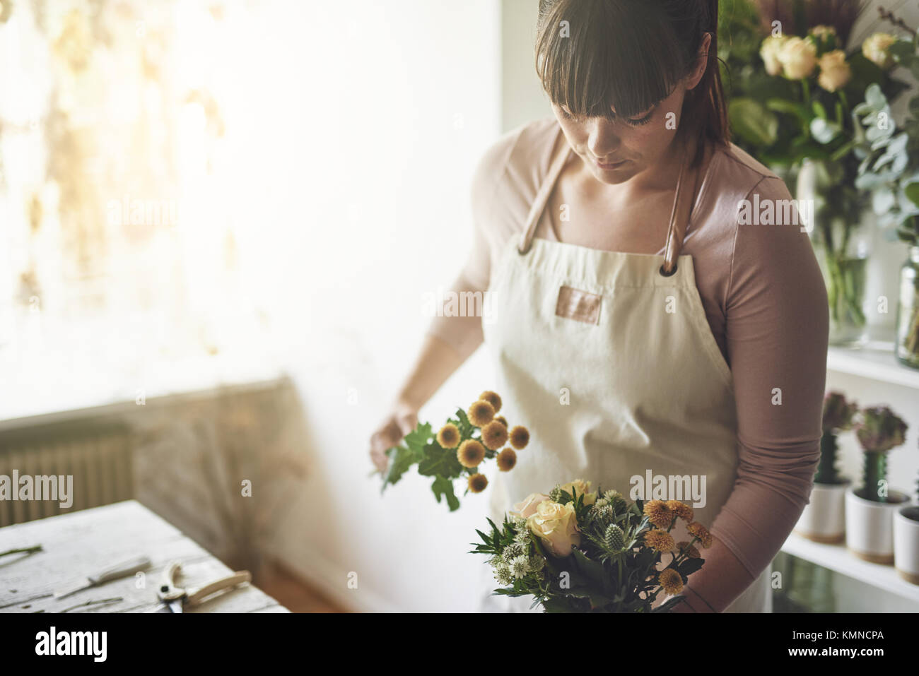 Young female florist working alone at a table in her flower shop making a mixed flower arrangement - Stock Image